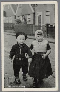 Jongen en meisje in dracht, gearmd staand in een straat. Het meisje draagt een versierd kraplapje en kanten mutsje. Bij het jongetje zijn de broeksknopen goed te zien. 1920-1930 #Urk