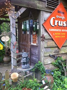 Small cabin in the woods with a gargoyle, wine bottle chandelier and orange crush sign. So fun