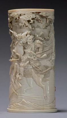 JAPAN    Pitong   carved ivory decorated in high   relief of battle scenes of samurai   background landscape with   pines and clouds Signature   red stamp in   Meiji Period   H: 23 cm