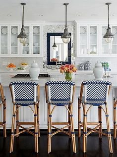 In the newly decorated kitchen, the only pieces that remained from the original design are the trio of antiqued steel pendants, which Cassie picked up on a drive through Franklin, TN. Blue and white bar stools add a dose of color and pattern, while white ginger jars on the bar counter keep things feeling clean and organized.