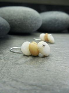 Tiny tiny beach pebbles stacked zen style dangle from clever little hooks of Sterling Silver. The natural colors of honey blonde, pale yellow, and neutral white are understated and organic. These whisper weight earrings are petite, but still have a subtle statement to make. A simple organic look to adorn your authentic self. Length: 1 inch, you get the earrings pictured ____________________________________________________  RootieBirds shop: www.etsy.com/shop/Rootiebirds ____________...