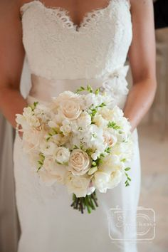 Leslie's bouquet features white ranunculus, white stock, cream roses, David Austin roses, and white freesia.