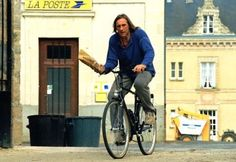 Gerard Depardieu rides a bike and holds a baguette. ¡Very french!
