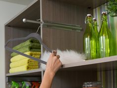 Installed in open shelving near the ironing board, a telescoping valet rod holds ironed shirts in a convenient spot.