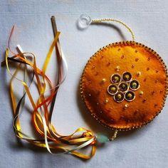 Móbile pendente de feltro com detalhes de fitas de cetim e guizos