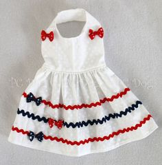 - Beautiful Patriotic Dress - White star print, with red and navy ric rac - Trimmed with matching star print bows - It easily attaches with adjustable velcro neck and belly straps - Open chest design Baby Dress Design, Baby Girl Dress Patterns, Dog Dresses, Little Girl Dresses, Girls Dresses, Puppy Clothes, Doll Clothes, Dress Clothes, Patriotic Dresses