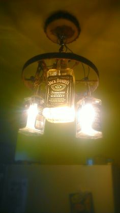 Wagon wheel and a few whiskey bottles upcycled into my new favorite light fixture! #jackdaniels #chandelier