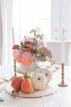 Simple fall centerpiece using seasonal fruit and grocery store flowers.
