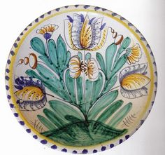 An English Delftware Tulip Charger, Late 17th Century, probably London, boldly painted with sprays of tulips, carnations and other flowers within a yellow line and blue dash border on the rim, diameter 13.5 in.