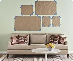 A tried and true method. Cut scrap paper to the size of the frame and mark the nail location on the paper. Using painters tape, move the paper templates around the wall until satisfied. Then hammer the nail through the marks. Remove the paper template and hang!