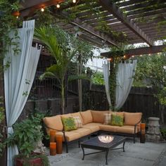 L-Shaped Couch with Cushions Shaded by Wooden Pergola with Curtain and String Lighting in Contemporary Patio Design Ideas