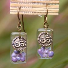 Cocoon Orchid Ohm Earrings   Playful dots of purple orchid glass are fused atop a clear rectangular base. These little beauties are adorned with a bronze ohm charm and dangle from bronze ear wire. Easy, everyday earrings. Each earring is individually and lovingly handmade. Because of this and based on how glass responds during the fusing process, item ordered may differ slightly from picture.  #YogaJewelry #YogaInspiredJewelry #Yoga