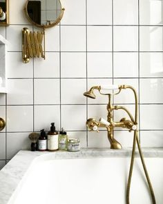 Here is a modern bathroom featuring another classic tile that we haven't seen lately - a good old square. Love the look with the darker grout and brass fixtures. That marble rimmed tub doesn't hurt either!