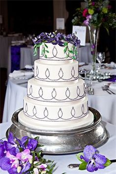 Andre : Four tier wedding cake with sugar purple Vanda Orchids and matching hand piped design finished with gros grain ribboning on marzipanned and iced moist rich fruit cake and fresh coffee and walnut sponge with whipped coffee buttercream filling