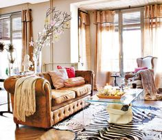 Loooove the matching copper tones on the couch and curtains with creamy tan walls and the ornamented branches bring an element of nature. The pink and red pillows bring a chic element too.