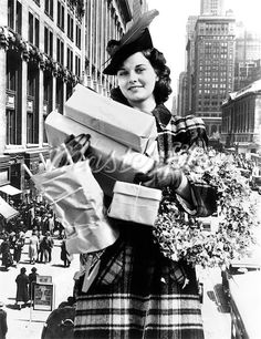 1930s 1940s WOMAN ARMS FULL CHRISTMAS SHOPPING PACKAGES & WREATH COMPOSITE WITH CITY STREET SCENE
