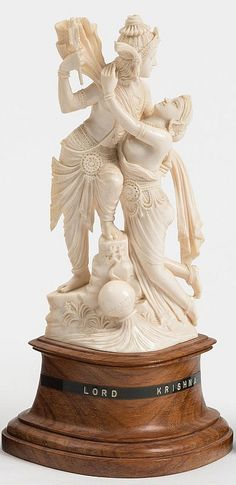 An Indian carved ivory figure: Lord Krishna mounted on a polished wood base, 23.5cm. high.