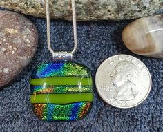 """Global Green"" is a handcrafted, holistic glass pendant that's been charged with positive Reiki energy. Made of gallery quality Dichroic and green glass, with detailed sterling silver plated bail, and"