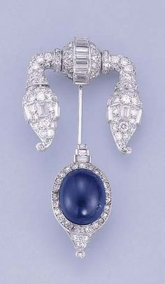 AN ART DECO SAPPHIRE AND DIAMOND JABOT PIN, BY BLACK, STARR & FROST The circular and baguette-cut diamond top with tapering stylised 'lantern' terminals, the opposite end with cabochon sapphire to the diamond surround, millegrain setting, circa 1930, 5.9 cm. high Signed BS for Black, Starr & Frost
