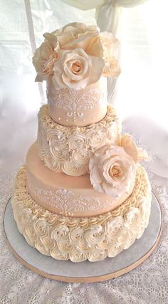 Piped rosette wedding cake with sugar flowers and lace piping. In peach, pink and cream.