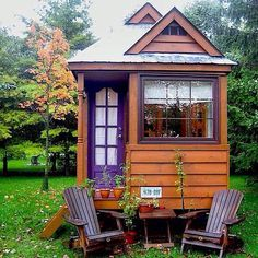 There's only one way to describe this tiny home with its purple door and wooden chairs: perfect.