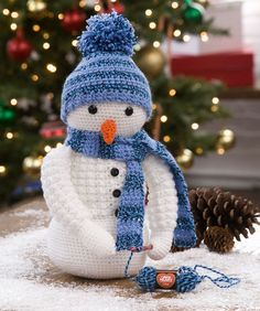 This friendly snowman is in the middle of crocheting himself a scarf! He's already wearing a textured cardigan and hat he made. Instructions for making mini ball of Red Heart Lisa are included.