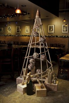 An modern Christmas tree by The Jubiltree Company, decorated with a cork garland and cork globe ornaments, illuminated from within by LED lights. Perfect for its wine bar home!  | The Jubiltree Company, LLC  | Modern Wood Christmas Trees