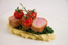 Stapel aus Schweinefilet, Kartoffel-Sellerie-Püree, Spinat und confierten Tomaten