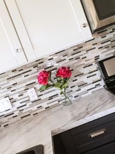 **Mosaic Glass Tile Backsplash | with metal in it. White and gray marble countertops.