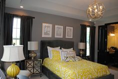 Master Bedroom. Bed centered between windows, with three pieces of art above headboard. Chandeleier.  Lose the yellow.