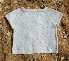 Den lille hvide top i let og luftigt båndgarn er en sikker vinder på en solrig sommerdag. Brug den til jeans med et lille kig til bar mave eller over en feminin sommerkjole. Toppen er i raglanfacon og strikkes på pinde nr. 5, så det går rimeligt stærkt, og hulmønsteret beskrives i strikkeopskriften. Sommertop med hulmønster Str. S – M…