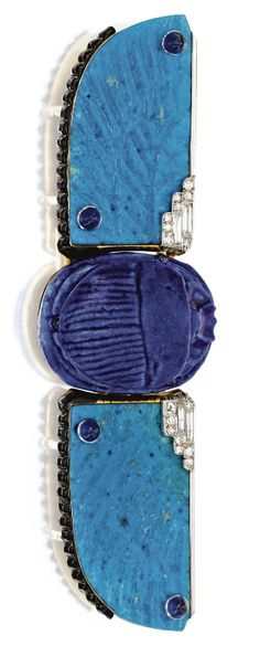 Egyptian-Style Jewelled Scarab Belt Buckle, Cartier, Paris, 1926. The hinged gold mounting centring a cobalt blue scarab flanked by turquoise faïence wings, all studded with small cabochon sapphires, the wings edged by round and baguette diamonds set in platinum and with black enamelled ridges, length 5 inches, signed Cartier, numbered, French assay mark, workshop mark. #Cartier #ArtDeco #buckle #EgyptianRevival