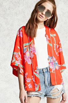 A satin kimono featuring an allover daffodil print, contrast piping, short sleeves, an open-front, and a vented hem.