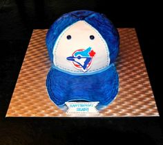 """This is one of our recent cakes that we were so excited to make. With the Toronto Blue Jays season freshly underway what better way to get into the baseball spirit than to whip up this """"throw back"""" Blue Jays baseball cap. Since our Toronto Blue Jays fan loves chocolate, we incorporated both Chocolate Milk Cake and Vanilla Cake that was filled with Chocolate Swiss Meringue Buttercream and according to our taste testers, this cake was a homerun!"""