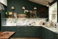 Bold green cabinets with marble countertops. Peckham Rye Kitchen' by deVOL
