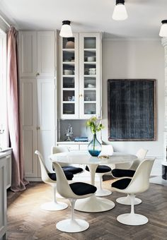 Bright and modern dining space with pretty contrats featuring a minimalistic round marble table and dining chairs from Eero Saarinen.