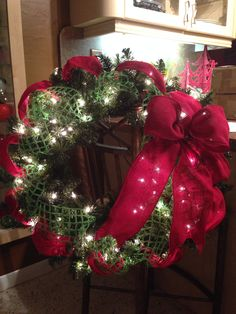 Evergreen wreath with red burlap bow.  Wreaths by Ileana