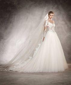 El vestido de novia ARLENE seduce solo de mirarlo por su corte a la cintura, manga larga, encaje en el escote barco con bordado y pedrería y falda voluminosa.