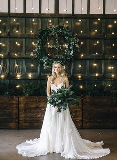 Cascading ruffles and a full skirt make for such a pretty silhouette in this Leanne Marshall Wedding Dress. This bride looks like a Grecian Goddess, especially with her wreath crown and green bouquet.