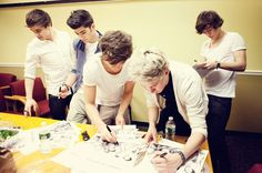 5:05PM: One Direction pre-signs autographs backstage.