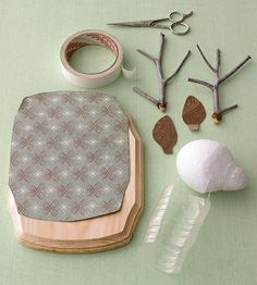 The materials you'll need- decorative paper, wooden plaque, masking tape, scissors, twigs, cardboard, plastic foam egg, and a plastic water bottle. Form the deer head by scraping a plastic foam egg shape at one end to make the nose. Cut ear shapes from thin cardboard. Fold one end of the ear to make a tab. Tape the ears to the head with masking tape, wrapping around the head