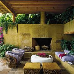 This outdoor room has a distinct Mexican atmosphere. Notice the equipal furniture and the adobe walls and fireplace.
