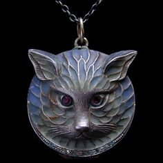 PLIQUE-A-JOUR CAT LOCKET A silver pendant, opening to reveal a mirror and a compartment for powder, with original powder-puff. Set rubies and diamond chips. German c.1910.