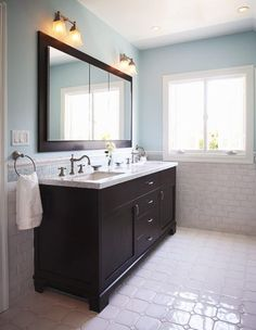 Dark cabinet & mirror frame, gray countertop, floor and shower tiles.  Blue/gray walls