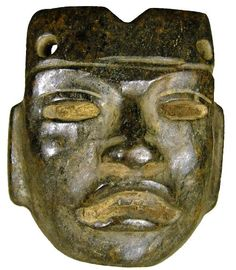Teotihuacán carved dark brown jade mask distinguishable by the serene expression, parted lips showing teeth, broad lips, open eyes under thinly arched brows, squared ears, circa 450 - 650 AD.