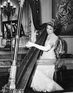 When film queen Grace Kelly assumes her real life role of 'her serene highness' Princess of Monaco, she might well enchant her Prince (Ranier III) with some serene notes on the palace harp (if any). Grace is shown trying her hand at the harp on the set of her recently completed but not yet released film 'The Swan.' The harp was used in several sequences in the romantic comedy.