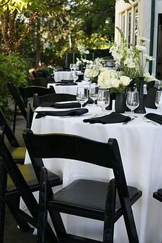 White Tablecloths Black Napkins Chairs And Flowers