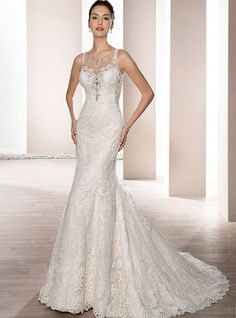 This striking sleeveless, fit n flare gown with a sheer neckline accented with lace and crystal beading features lace over sheer side panels that continues into the dramatic back with button closure and Chapel train.