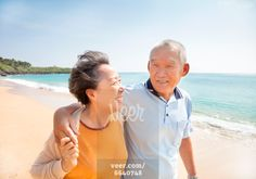 happy asian seniors walking on the beach Stock Photo