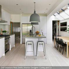 Die moderne Küche ist praktisch und stilvoll zugleich eingerichtet. Auf dem Tresen, über dem große Pendelleuchten hängen, kann man kochen, während die Gäste …